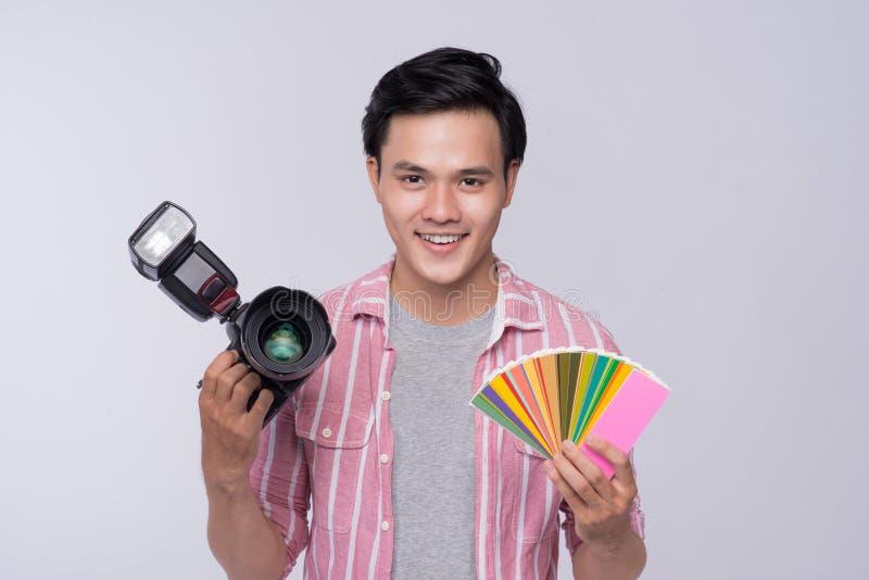拿着数字照相机的年轻亚裔摄影师,当工作i时 库存图片