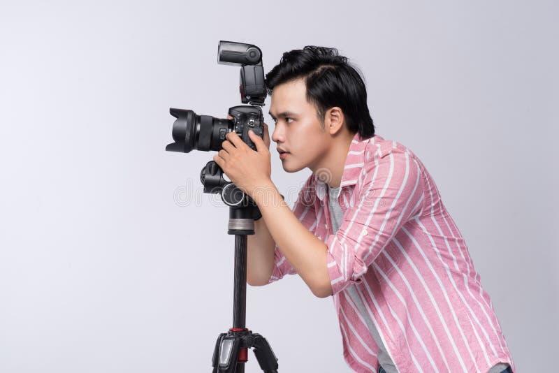拿着数字照相机, wh的年轻亚裔摄影师侧视图  图库摄影