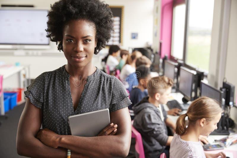 拿着数字片剂高中生的教学线女老师画象坐由在计算机类的屏幕 免版税图库摄影