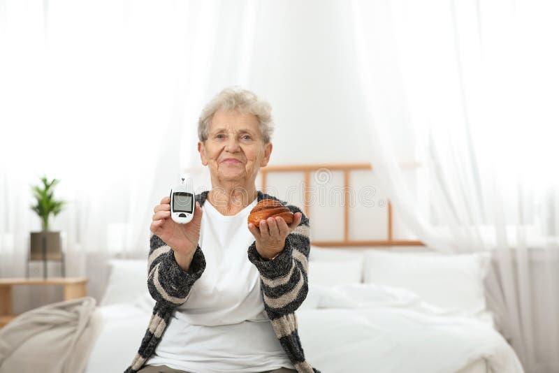 拿着数字glucometer和酥皮点心的资深妇女 糖尿病饮食 免版税库存照片