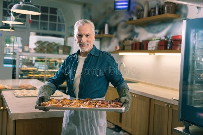 拿着整个盘子用美味的桂香小圆面包的放光的灰发的面包师 免版税库存照片