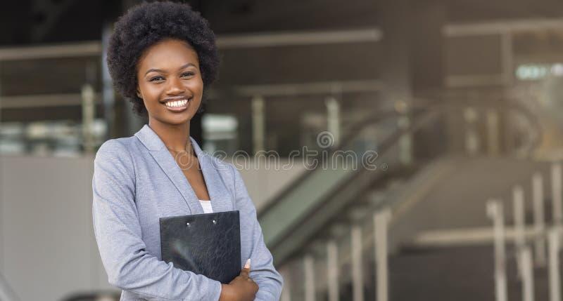 拿着文件夹的美丽的蓬松卷发女商人,看照相机 免版税图库摄影