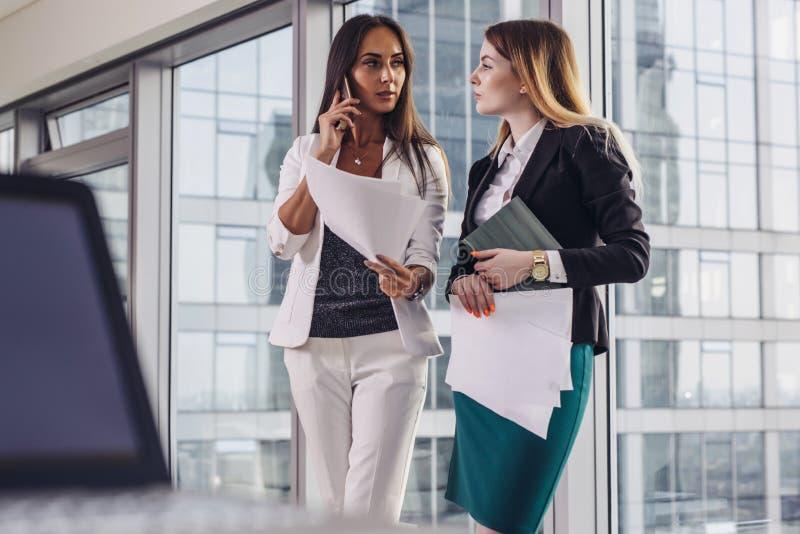 拿着文件的两名女实业家谈话与他们的顾客由提供不同的解答的手机站立  免版税库存照片