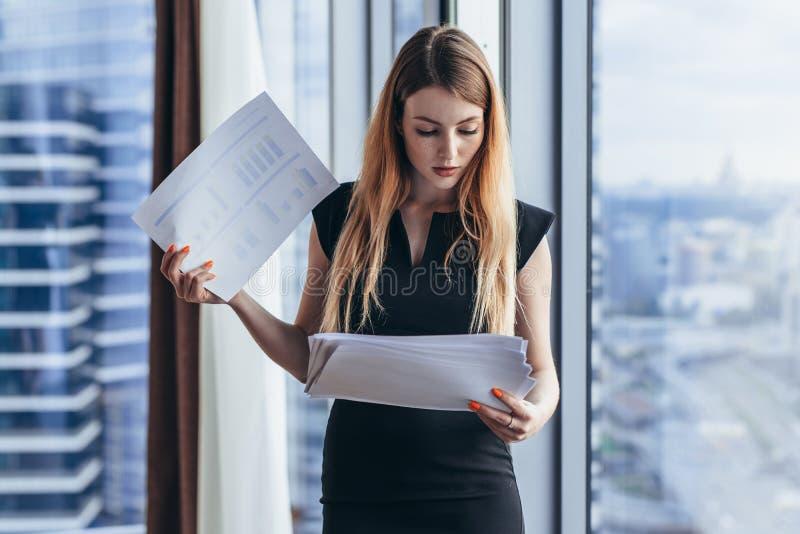 拿着文件的确信的女性主任站立在现代办公室反对全景窗口 库存图片