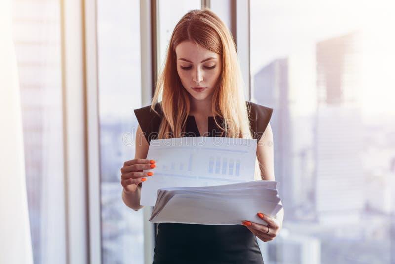拿着文件的确信的女性主任站立在现代办公室反对全景窗口 免版税库存图片