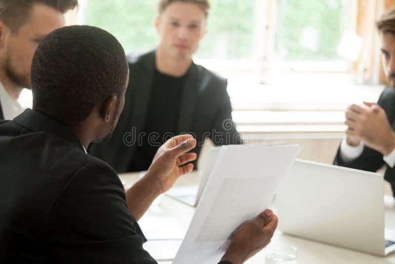 拿着文件谈话与伙伴,关闭的非洲商人 库存图片