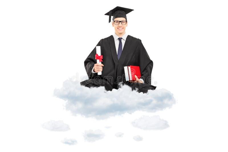 拿着文凭和书的男性大学毕业生供以座位在云彩 免版税库存图片