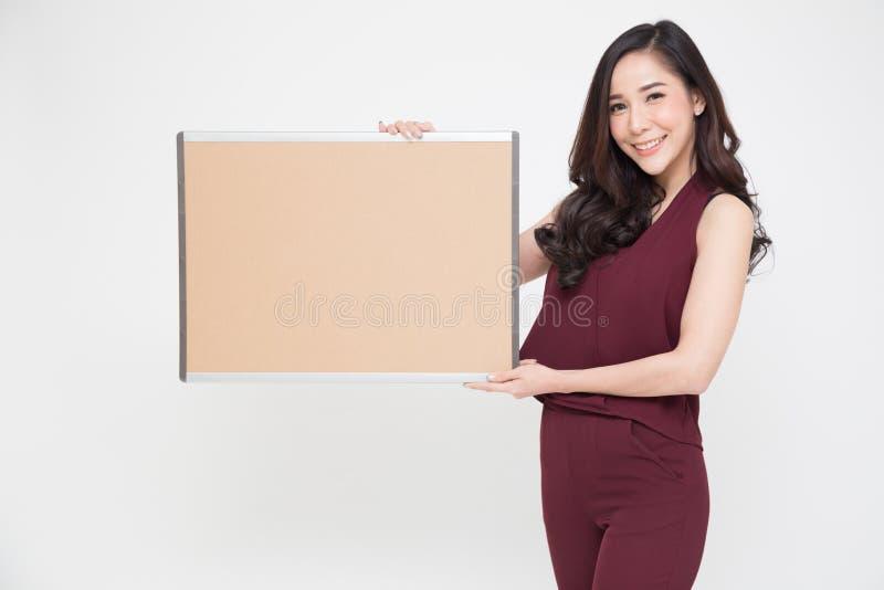 拿着文本或广告的美丽的亚裔女孩一张空白的海报, 免版税库存照片