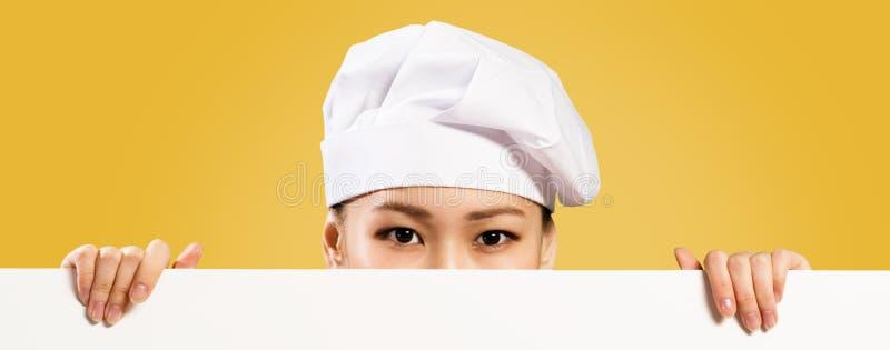 拿着文本的亚裔女性厨师海报 免版税库存图片