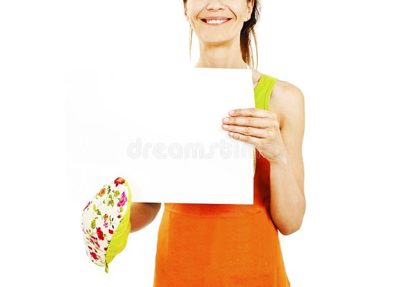拿着文本的主妇佩带的厨房围裙空白的标志拷贝空间 免版税库存照片