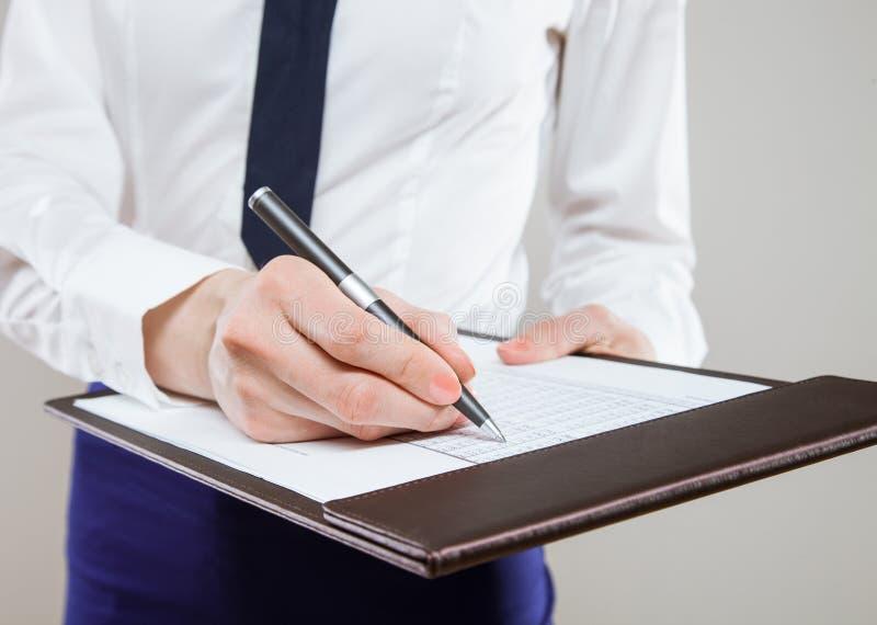 拿着文件和笔的无法认出的年轻女实业家 免版税库存图片