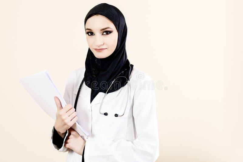 拿着文件的一件白色外套的回教女性医生 免版税库存图片