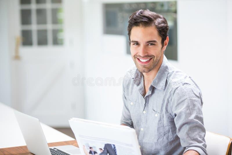 拿着文件的微笑的年轻人,当坐在有膝上型计算机的时书桌 免版税图库摄影