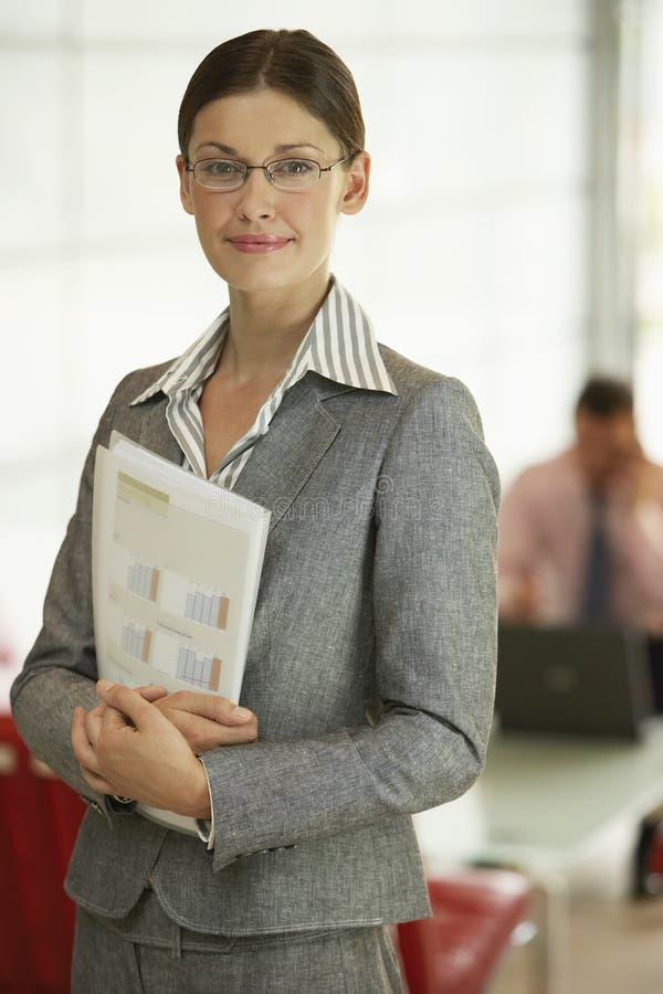 拿着文件的确信的女实业家在办公室 库存图片