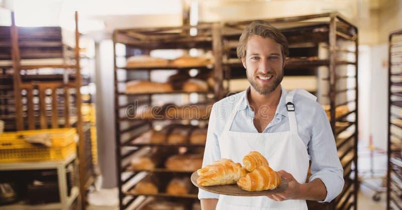 拿着新月形面包的愉快的小企业主人 图库摄影