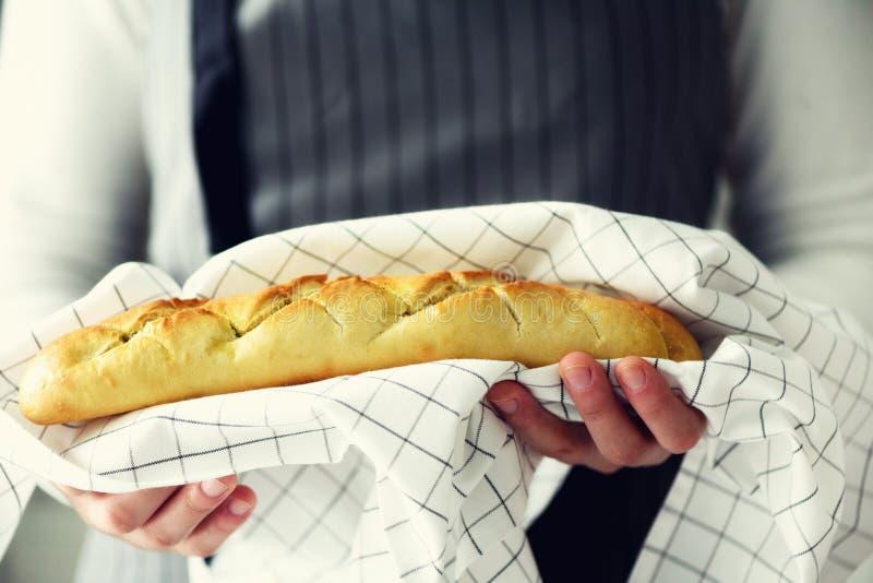 拿着新近地被烘烤的面包的妇女手 法国长方形宝石,面包店概念,自创食物,健康吃 复制空间 免版税图库摄影