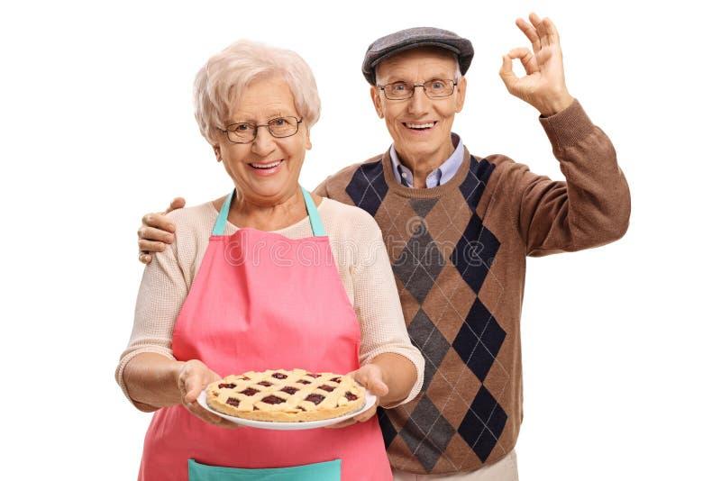 拿着新近地被烘烤的饼和年长人的年长妇女做o 免版税库存照片