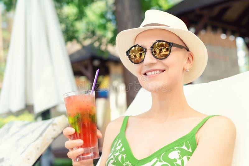 拿着新鲜的冷的草莓mojito鸡尾酒的年轻愉快的妇女享受假期在手段在热的好日子 秃头年轻的白种人 免版税库存图片