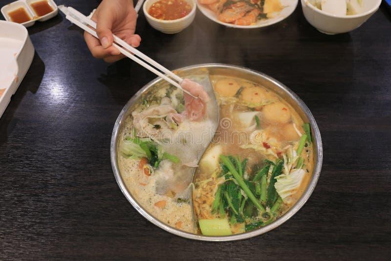 拿着新鲜的切的猪肉的筷子妇女手未加工与烹调的菜或shabu shabu和sukiyaki在火锅, 免版税库存照片