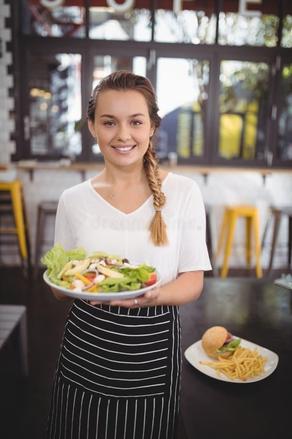 拿着新鲜的希腊生菜盘的微笑的年轻女服务员画象  免版税图库摄影