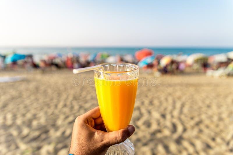 拿着新鲜的杯与秸杆的橙汁的一个人在海滩前面 库存图片