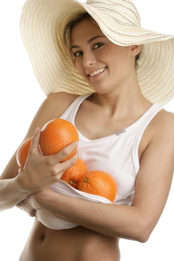 拿着新鲜的水多的桔子的少妇佩带的草帽 库存照片