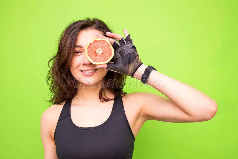 拿着新鲜的粉红色葡萄柚的年轻深色的健身妇女滑稽的画象  健康吃生活方式和减重概念 义卖市场 免版税库存照片