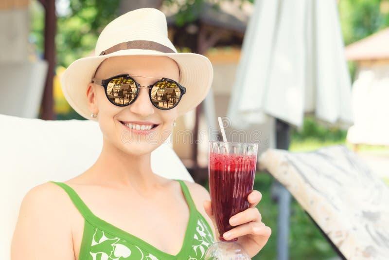 拿着新鲜的莓果圆滑的人鸡尾酒的年轻愉快的妇女享受假期在手段在热的好日子 年轻白种人秃头妇女 免版税库存照片