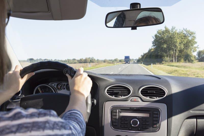 拿着方向盘的妇女` s手的特写镜头 女孩司机在汽车的轮子后乘坐 免版税库存图片