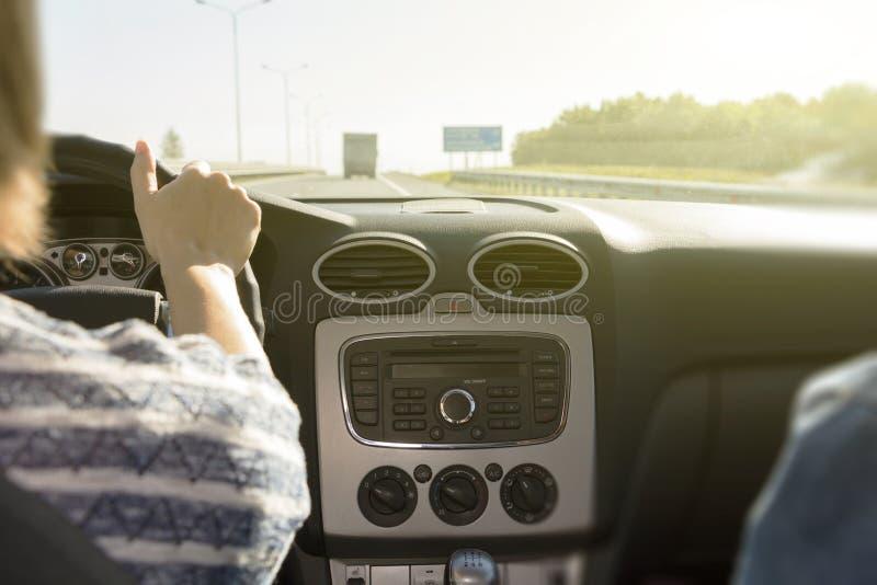 拿着方向盘的妇女` s手的特写镜头 女孩司机在汽车的轮子后乘坐 免版税库存照片