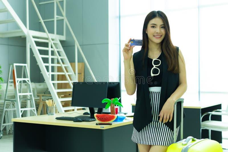 拿着旅行的一名美丽的亚裔妇女信用卡 免版税库存照片