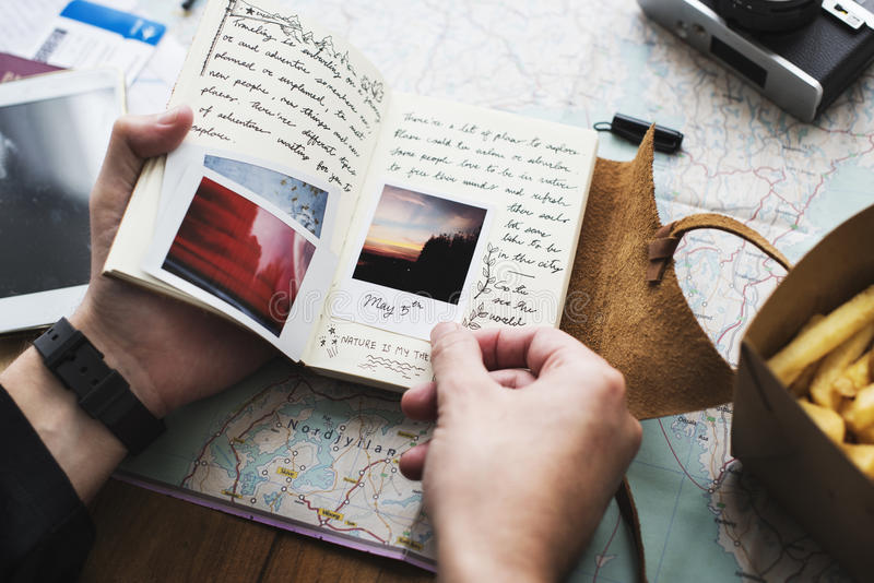拿着旅途在地图backgro的手特写镜头日志笔记本 免版税库存图片