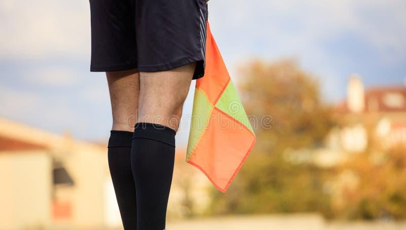 拿着旗子的领域的足球辅助裁判员 被弄脏的背景 免版税图库摄影