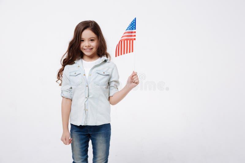 拿着旗子的高兴小女孩在演播室 免版税图库摄影