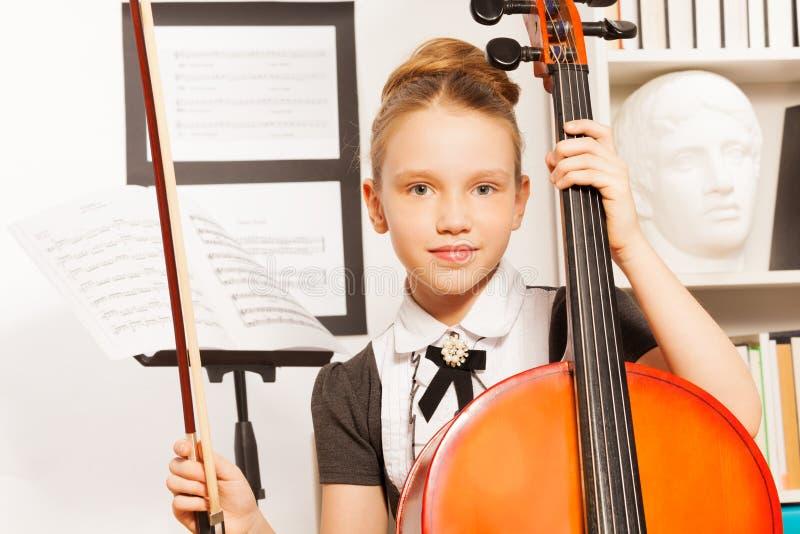 拿着无意识而不停地拨弄弓的女孩画象弹大提琴 库存图片