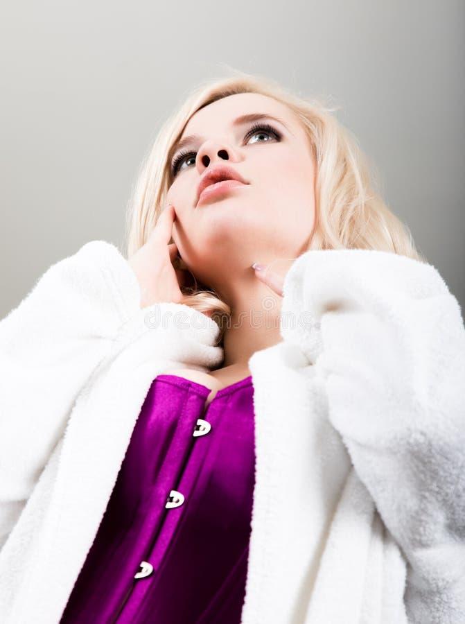 拿着日光灯的束腰、长袜和浴巾的性感的美丽的白肤金发的妇女坐床 库存图片