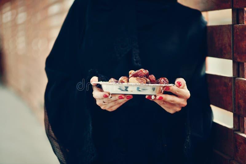 拿着日期板材的Emarati阿拉伯妇女 免版税库存照片