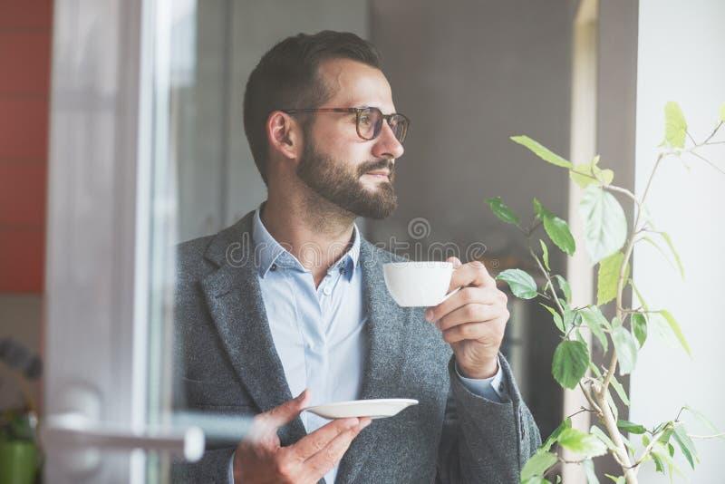 拿着早晨咖啡的商人 免版税库存照片