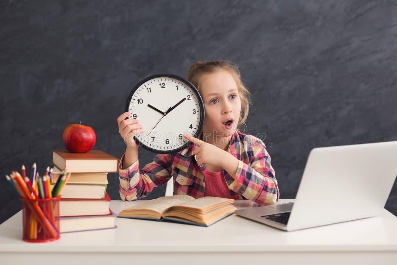 拿着时钟和指向对此的逗人喜爱的聪明的女孩 免版税图库摄影