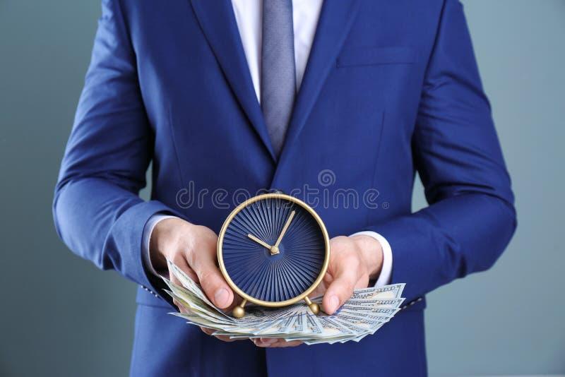 拿着时钟和金钱在颜色背景的商人 时间安排 库存图片
