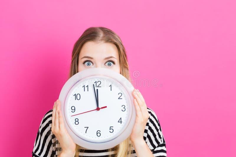 拿着时钟的妇女显示几乎12 库存图片