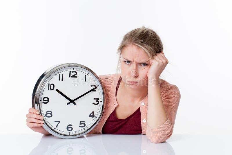 拿着时钟的抱怨的美丽的少妇 免版税库存照片