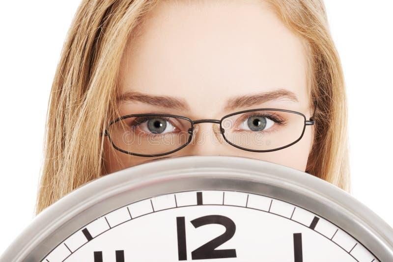 拿着时钟的白种人女商人。 免版税图库摄影