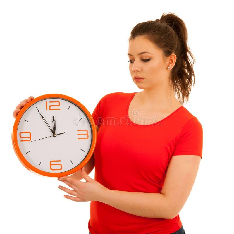 拿着时钟的逗人喜爱的妇女作为时间安排simbol  图库摄影
