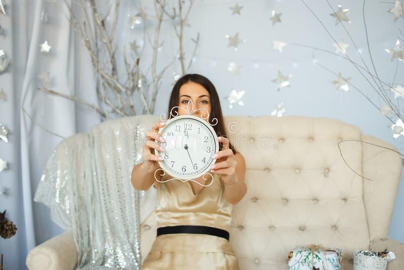 拿着时钟的金礼服的妇女 免版税库存图片