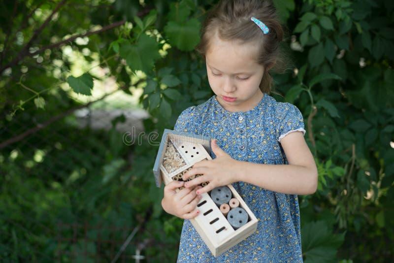 拿着昆虫旅馆的女孩 库存照片
