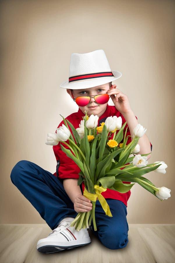 拿着春天郁金香的花束帽子的时髦的男孩 儿童` s时尚 妇女` s天,母亲` s天 图库摄影