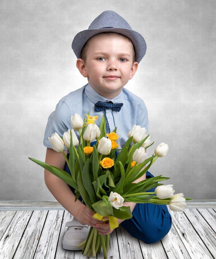 拿着春天郁金香的花束帽子的时髦的男孩 儿童` s时尚 库存图片