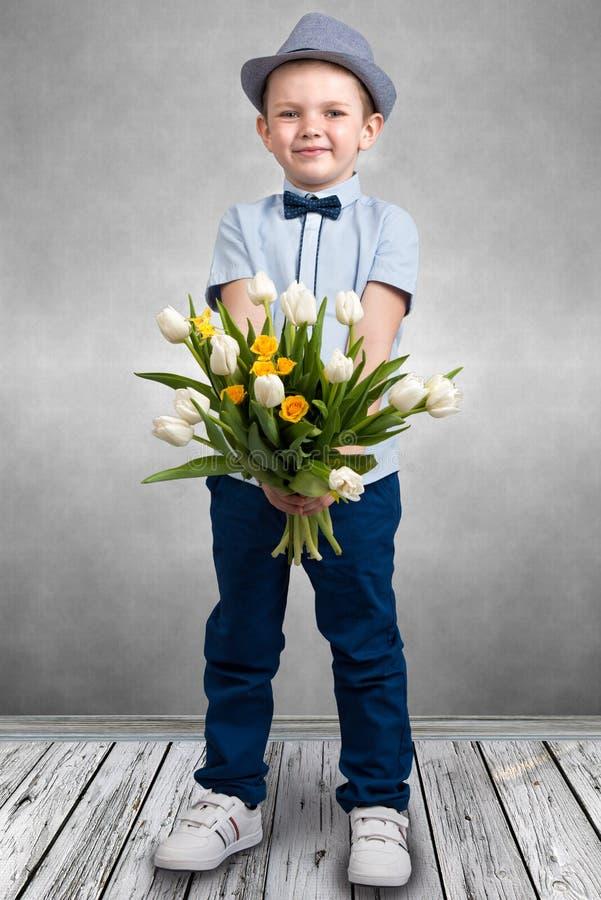 拿着春天郁金香的花束帽子的时髦的男孩 儿童` s时尚 免版税库存照片