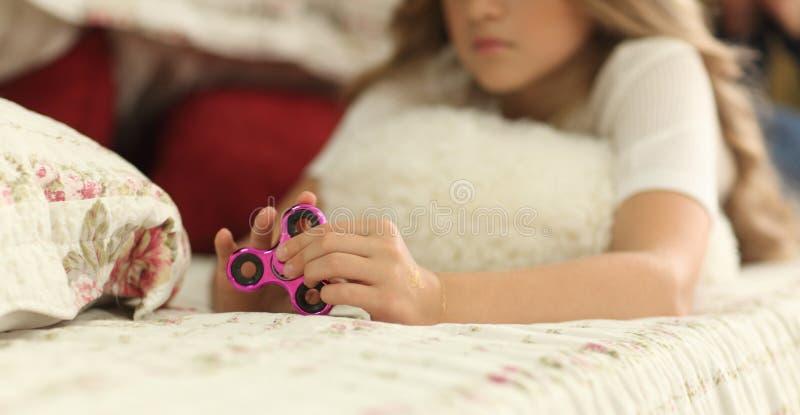 拿着普遍的坐立不安锭床工人玩具的青少年女孩-特写镜头集中于锭床工人,家内部 图库摄影